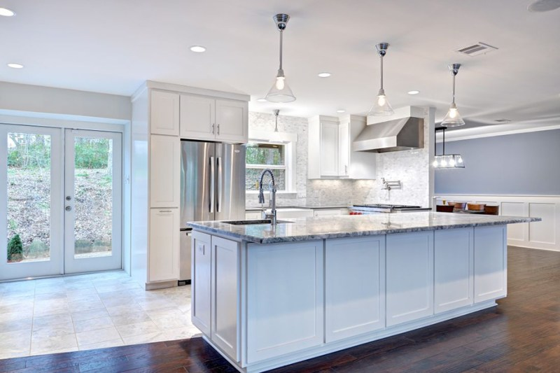 White kitchen with with vaulted ceiling. Kitchen with glass pendant lights over white kitchen island with granite countertop