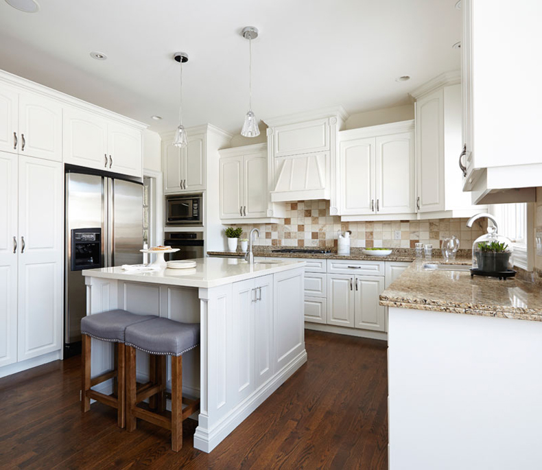 Small white kitchen with gray leather bar stools. Kitchen with glass mini pendant lights over white kitchen island with marble countertop
