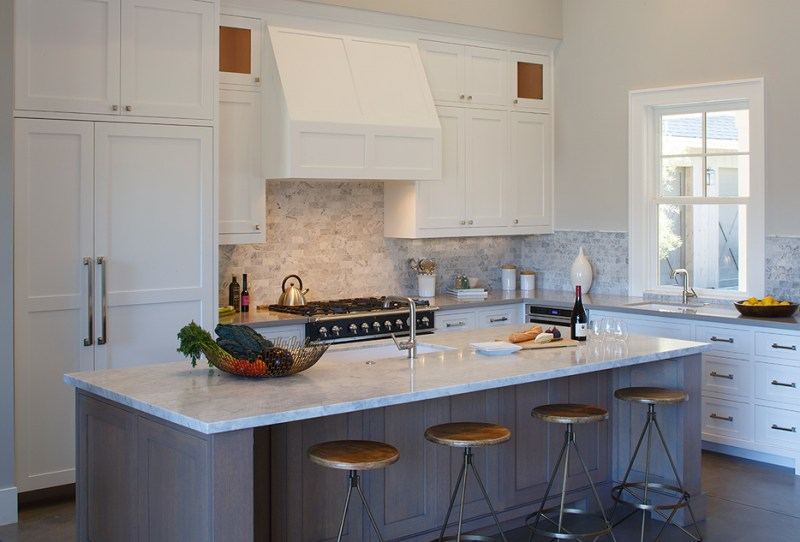 White kitchen with gray kitchen island with marble countertop and bar stools