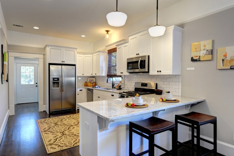 Small white kitchen with white tile backsplash and bar stools. Kitchen with white pendant lights over kitchen island with marble countertop