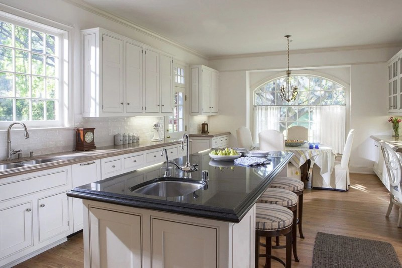 White kitchen with dining room combination with dark quartz countertop and bar stools