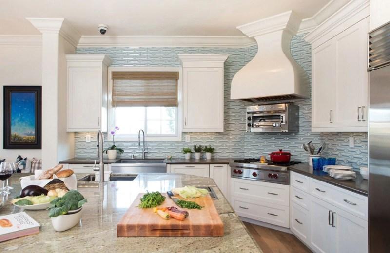 White kitchen with turquoise tile backsplash and dark quartz countertop
