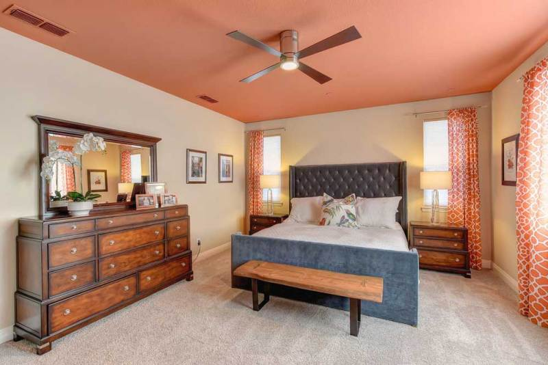 orange bedroom with ceiling fan lighting