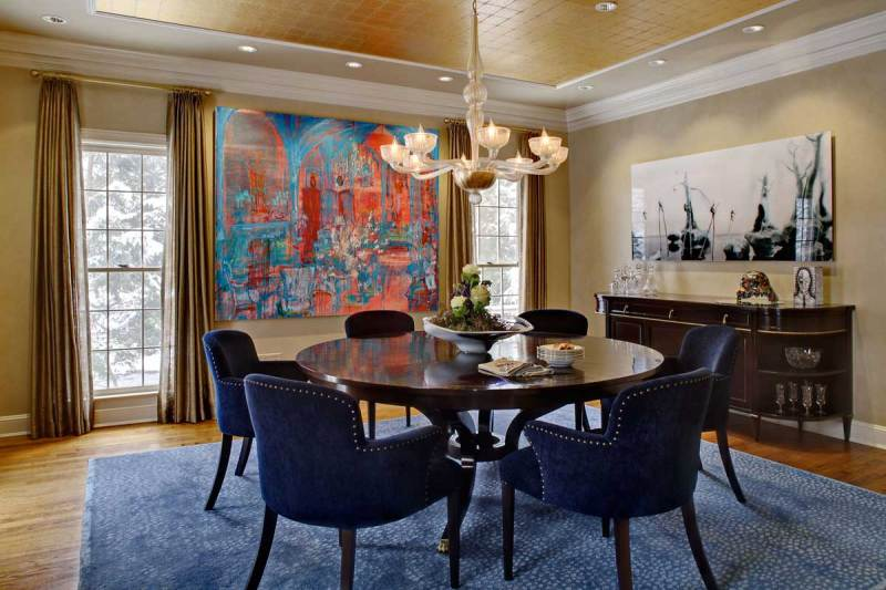 transitional dining room with chandelier and navy chairs