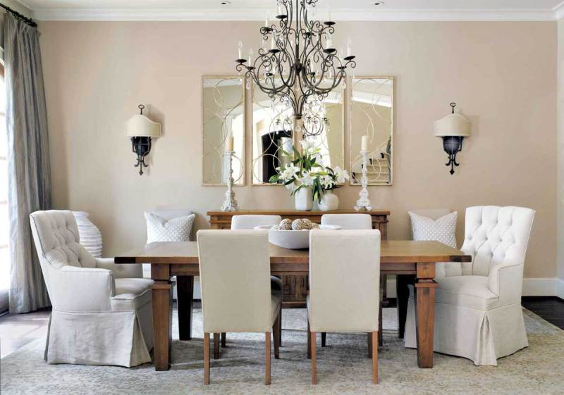 dining room with chandeliers and wall sconces
