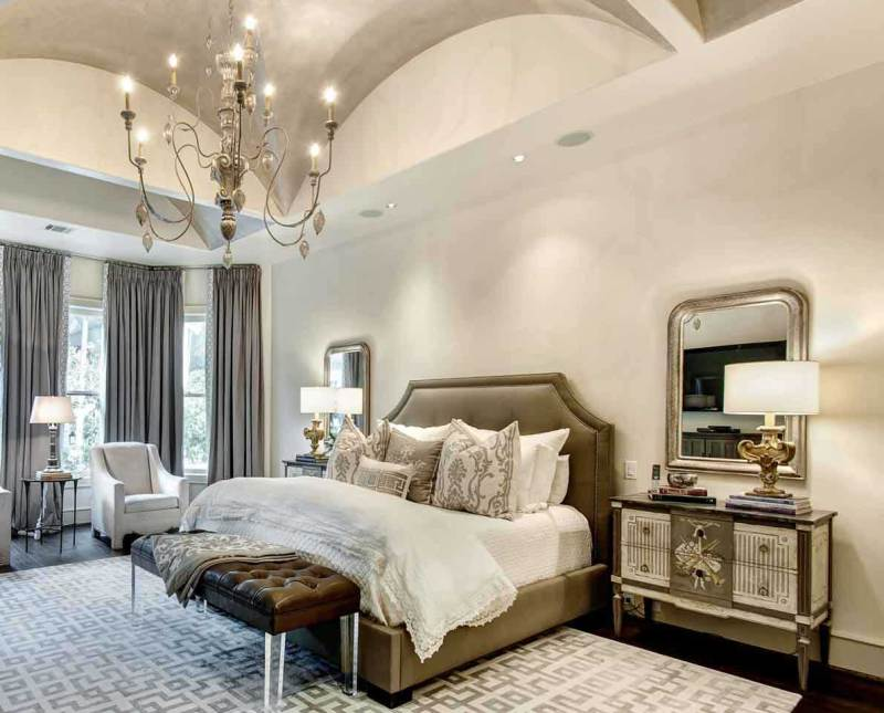 white master bedroom with chandle chandelier and table lamps