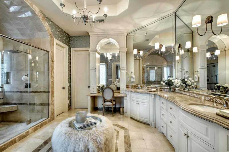 master bathroom with wall sconces and candle chandelier
