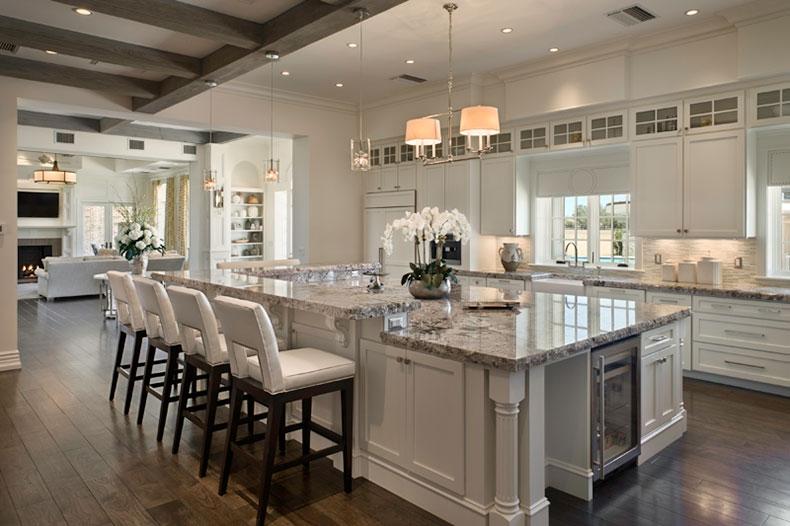 Bianco antico granite countertops with white cabinets and dark wood floring