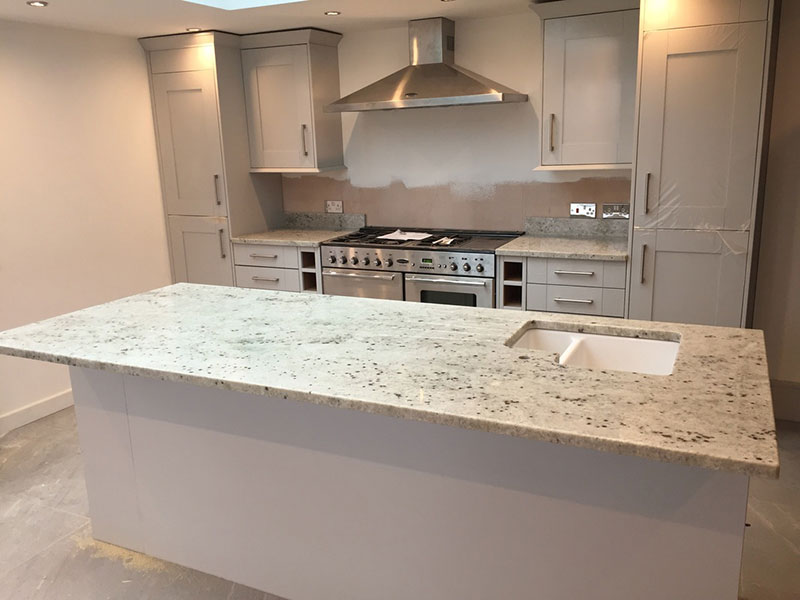 Colonial white granite countertops pictures cost pros for Granite on white cabinets
