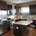 Contemporary kitchen with dark cabinets and bianco romano granite