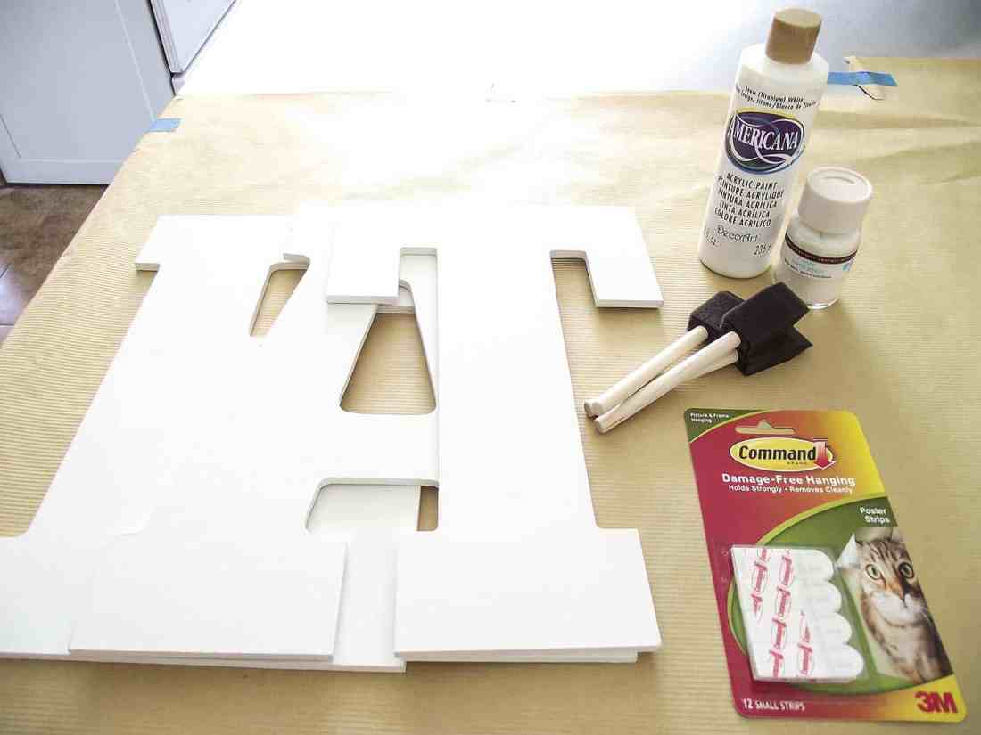 Supplies for Giant Glitter EAT sign for kitchen: wood craft letters, foam brushes, glue, paint, command strips.