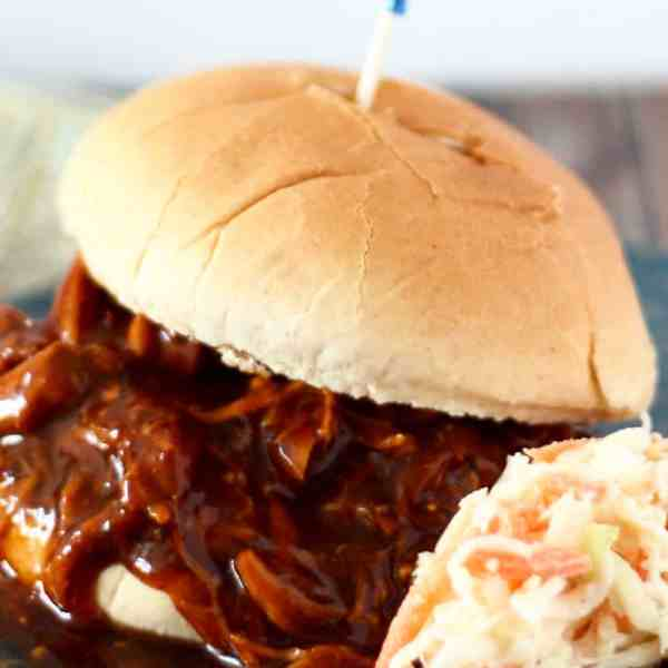 pulled chicken sandwich on a plate with coleslaw
