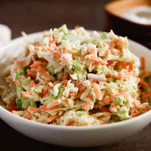 coleslaw in a white bowl on a dark table
