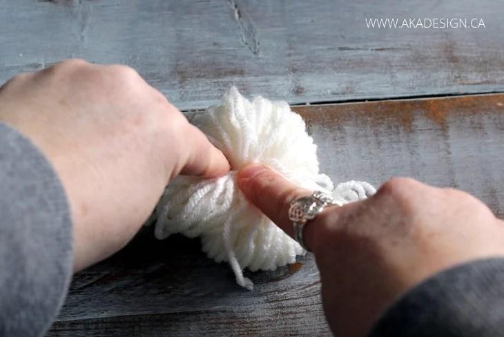 tie a knot around pom poms