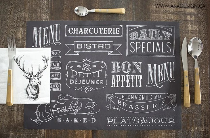 wood table, chalkboard paper placemat, wooden utensils, stag head napkin