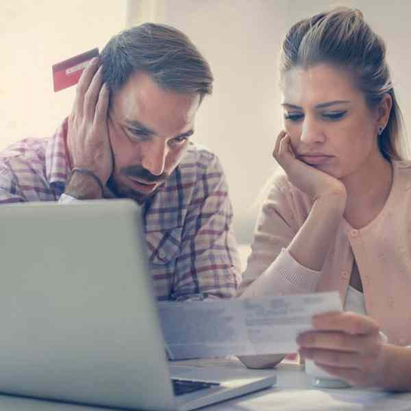 couple looking at bills wondering how to get out of debt