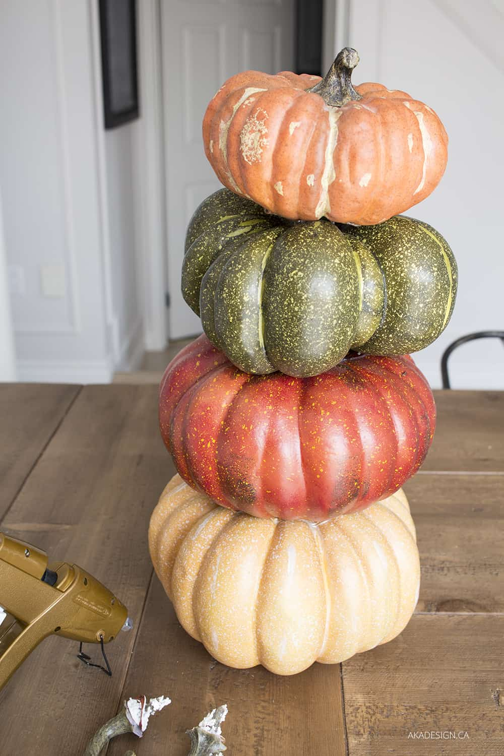 four faux pumpkins stacked in a tower