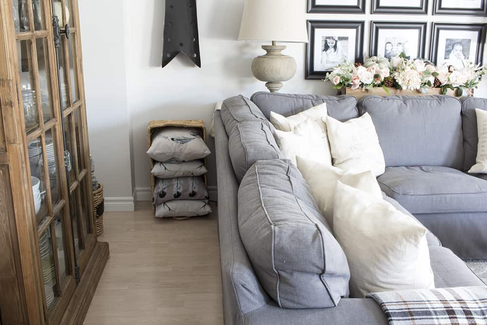 grey sectional, wood cabinet, basket of pillows