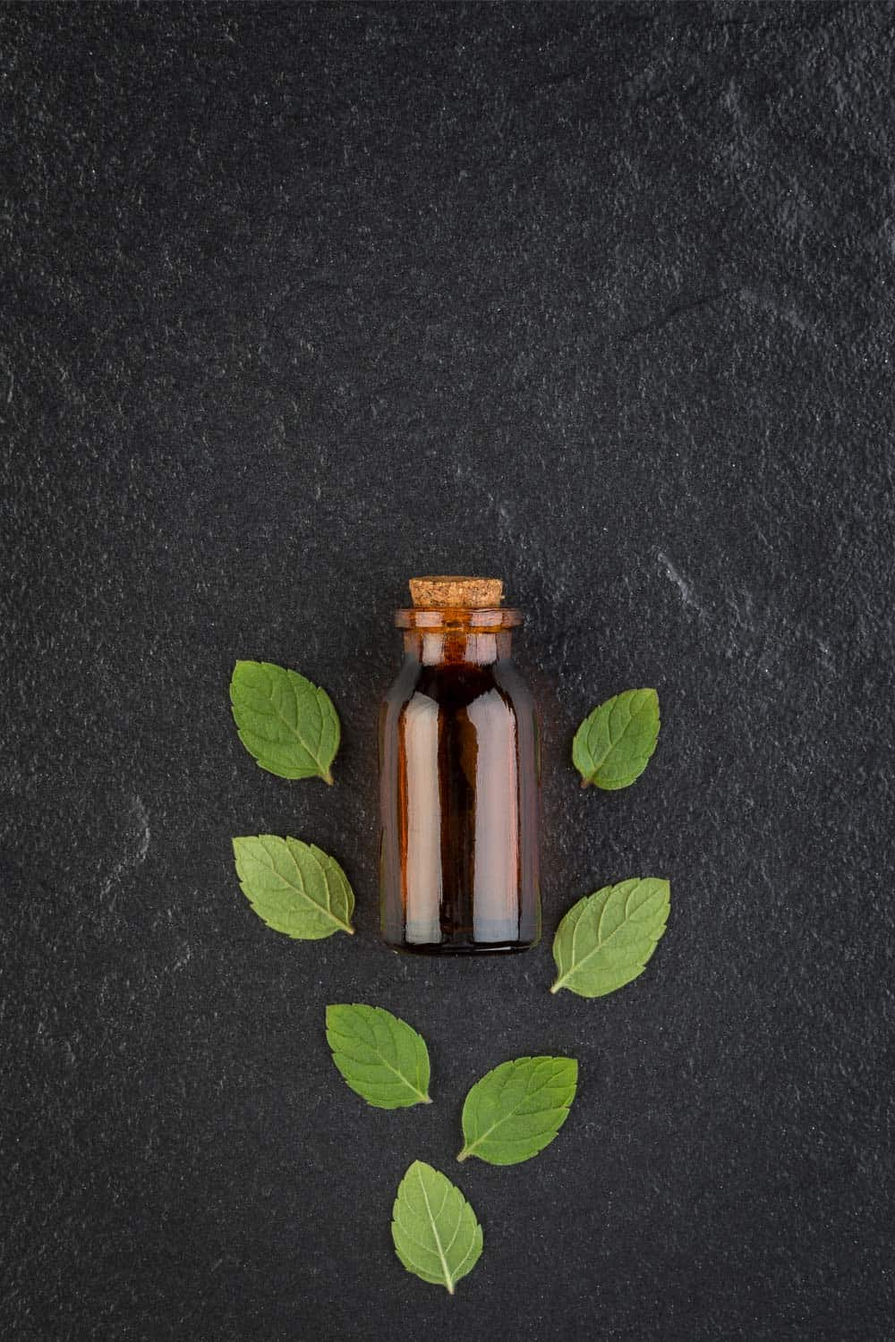 essential oils to avoid for pets and babies on black background with amber roller bottle