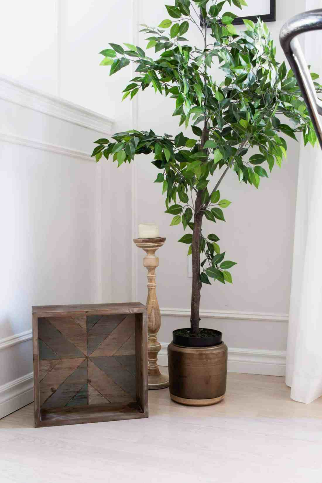 Faux tree in a pot with decorative box and candlestand.