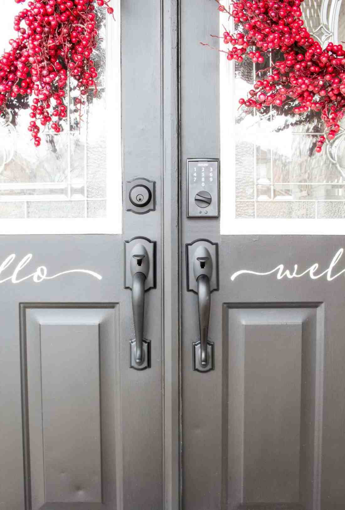 black double front doors with black hardware and red wreaths