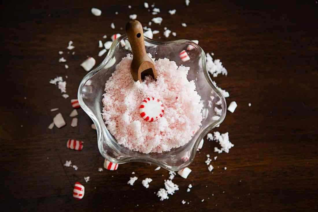 pink peppermint sugar scrub in a bowl with wood scoop