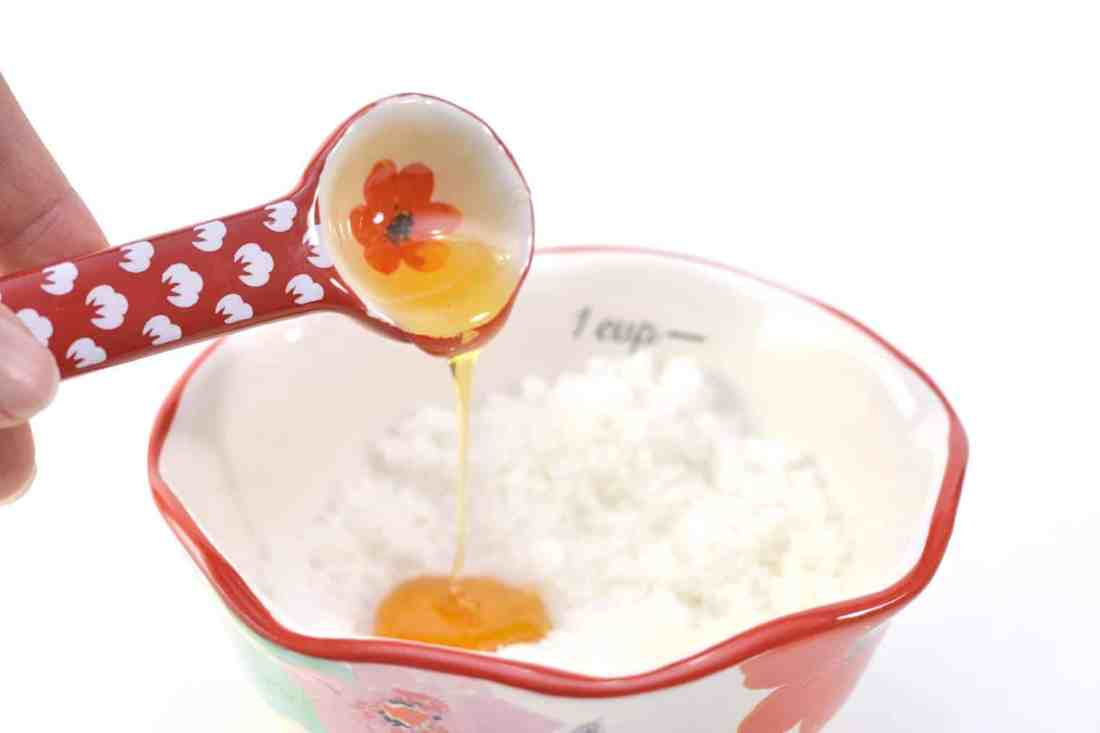 adding honey to oil and sugar mix