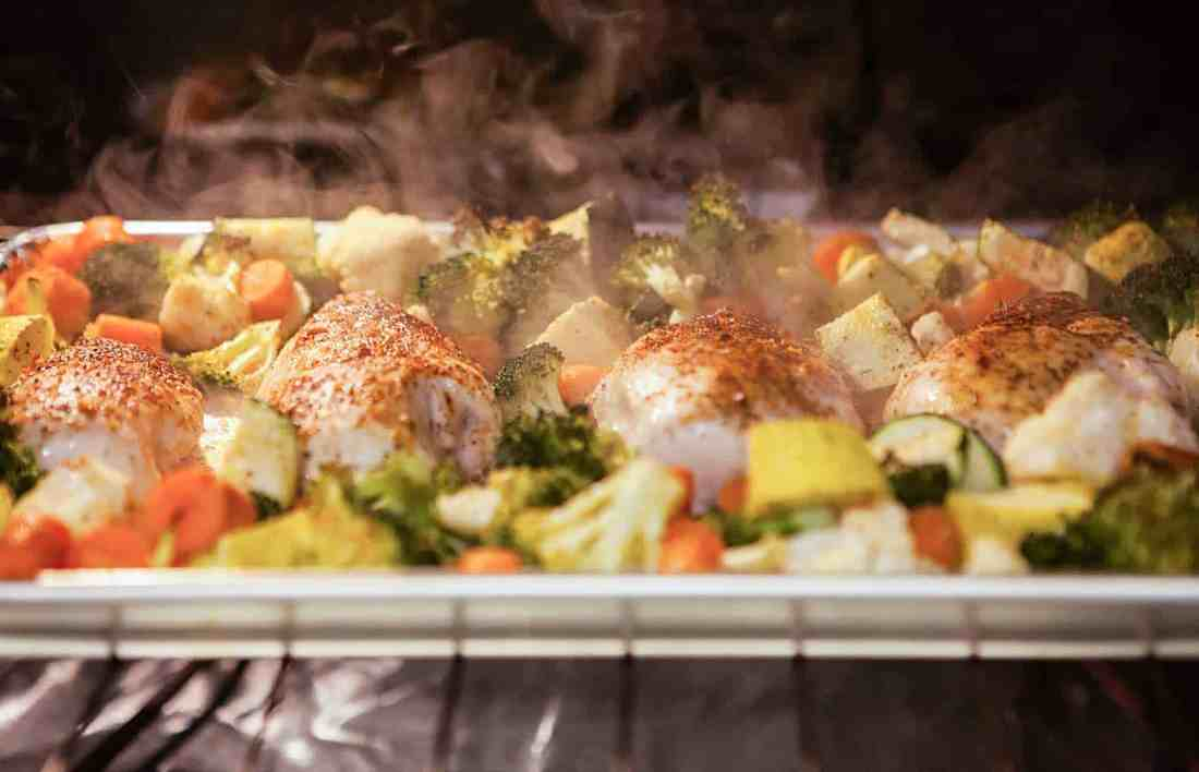 chicken and veggies on foil-lined pan in the oven steaming