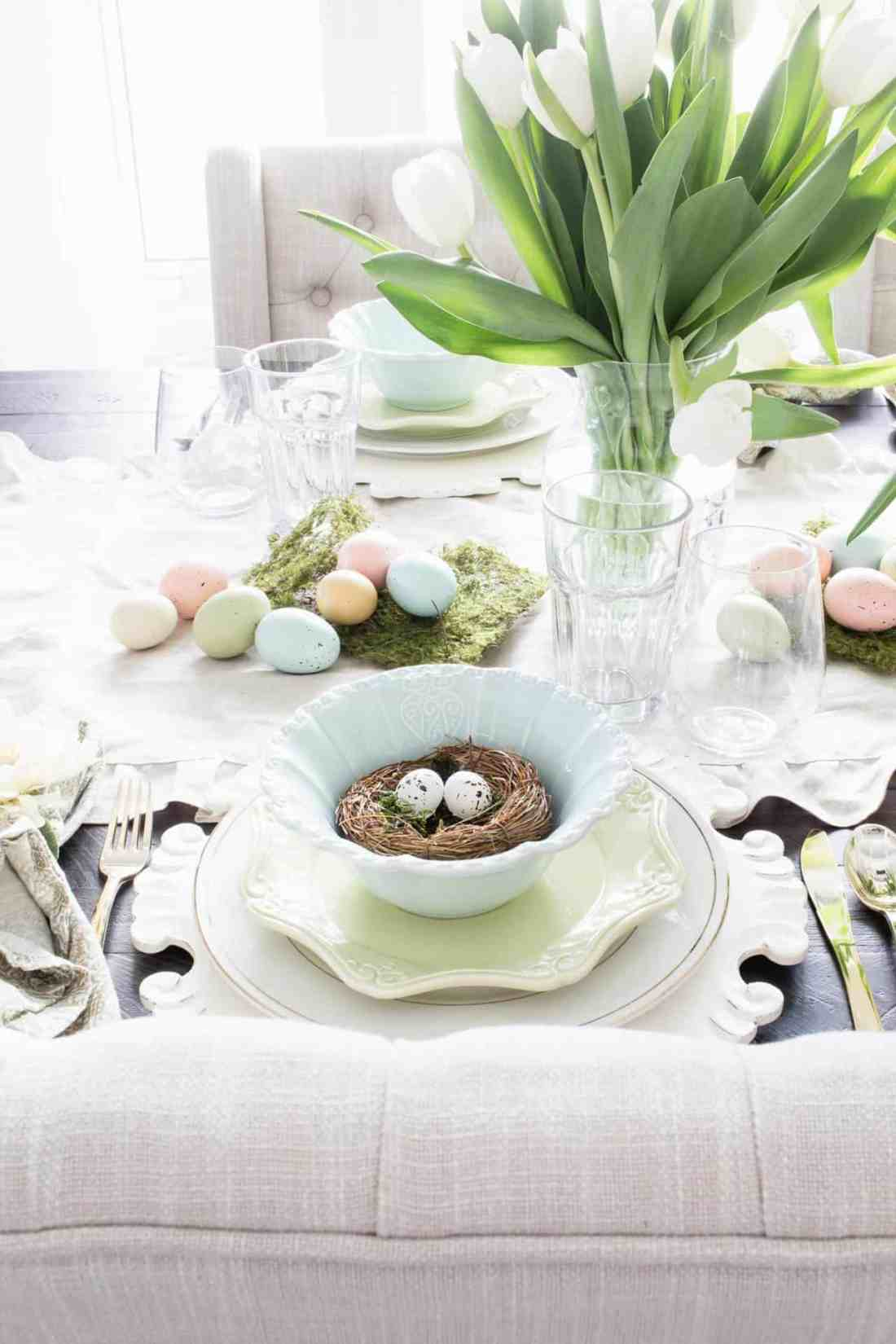 spring table setting with ruffled linen runner, faux moss and pastel easter egg decor