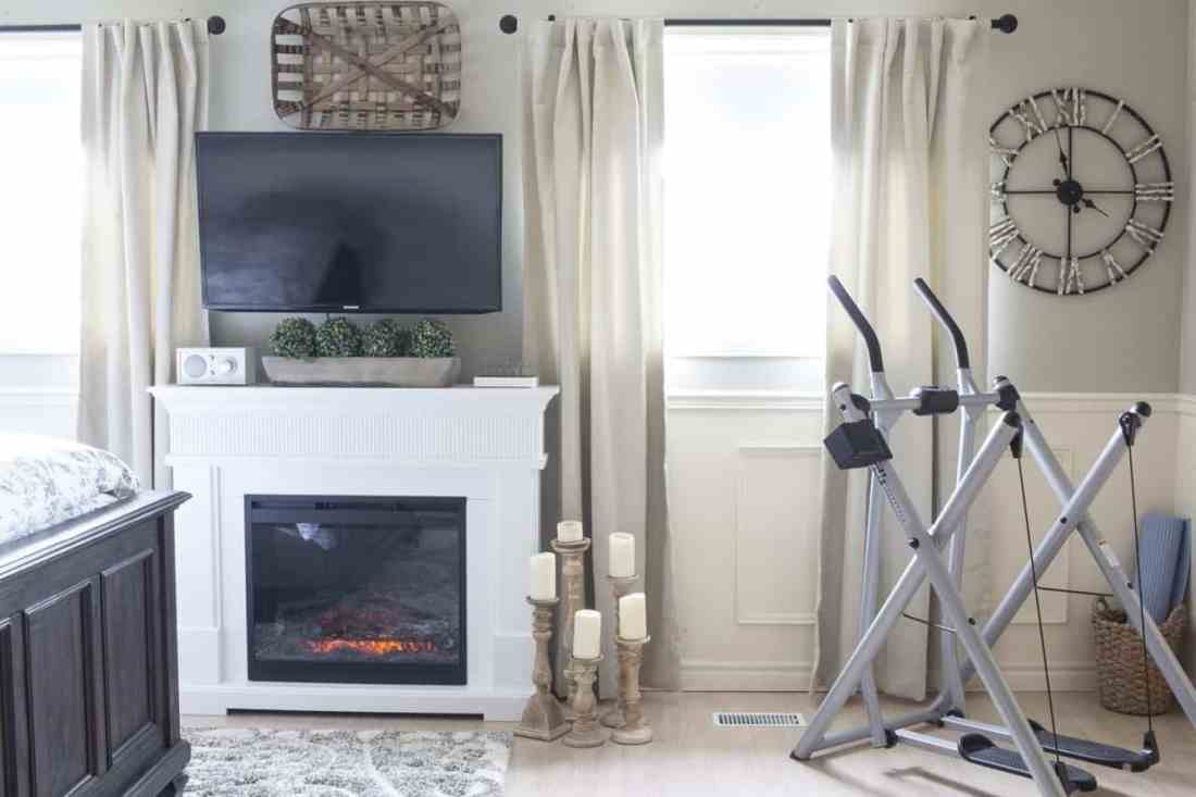 Master bedroom with fireplace and exercise equipment