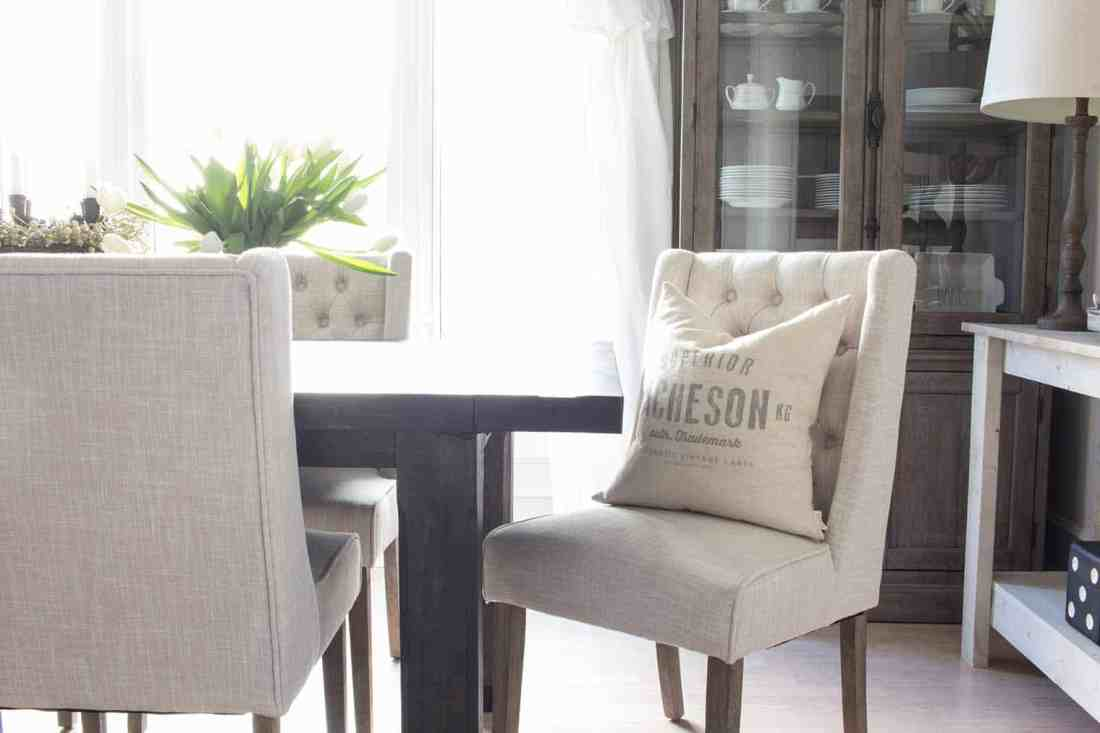 tufted wingback dining chair with custom pillow at dining room table