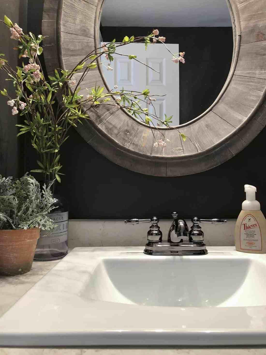 Wood oval mirror black walls white sink black faucet