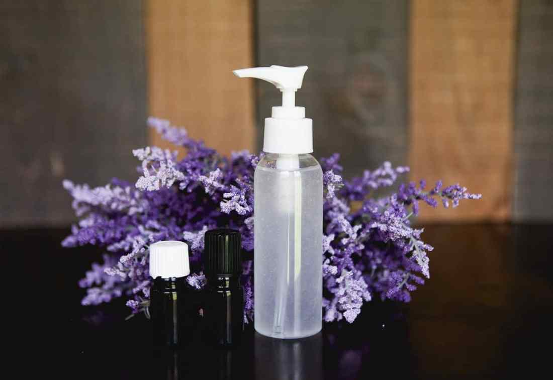 homemade hand sanitizer with essential oils pump bottle on table with lavender
