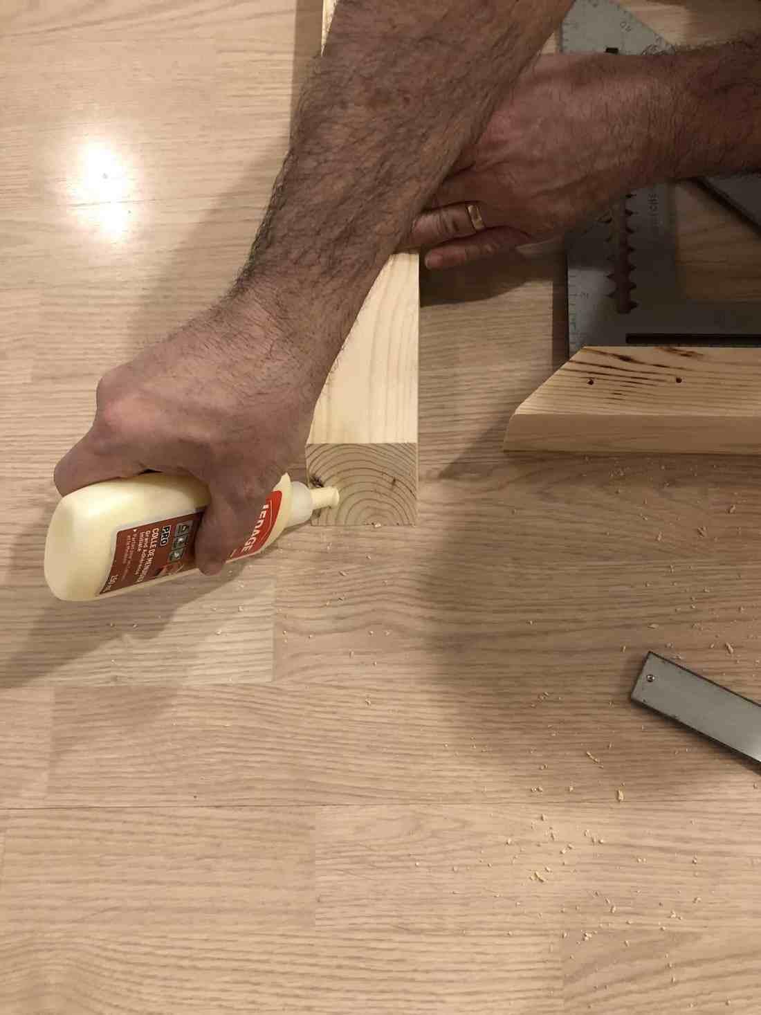 man gluing wood