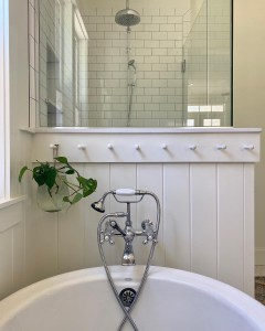 propagating pothos plant hanging in a glass vase in a master bathroom