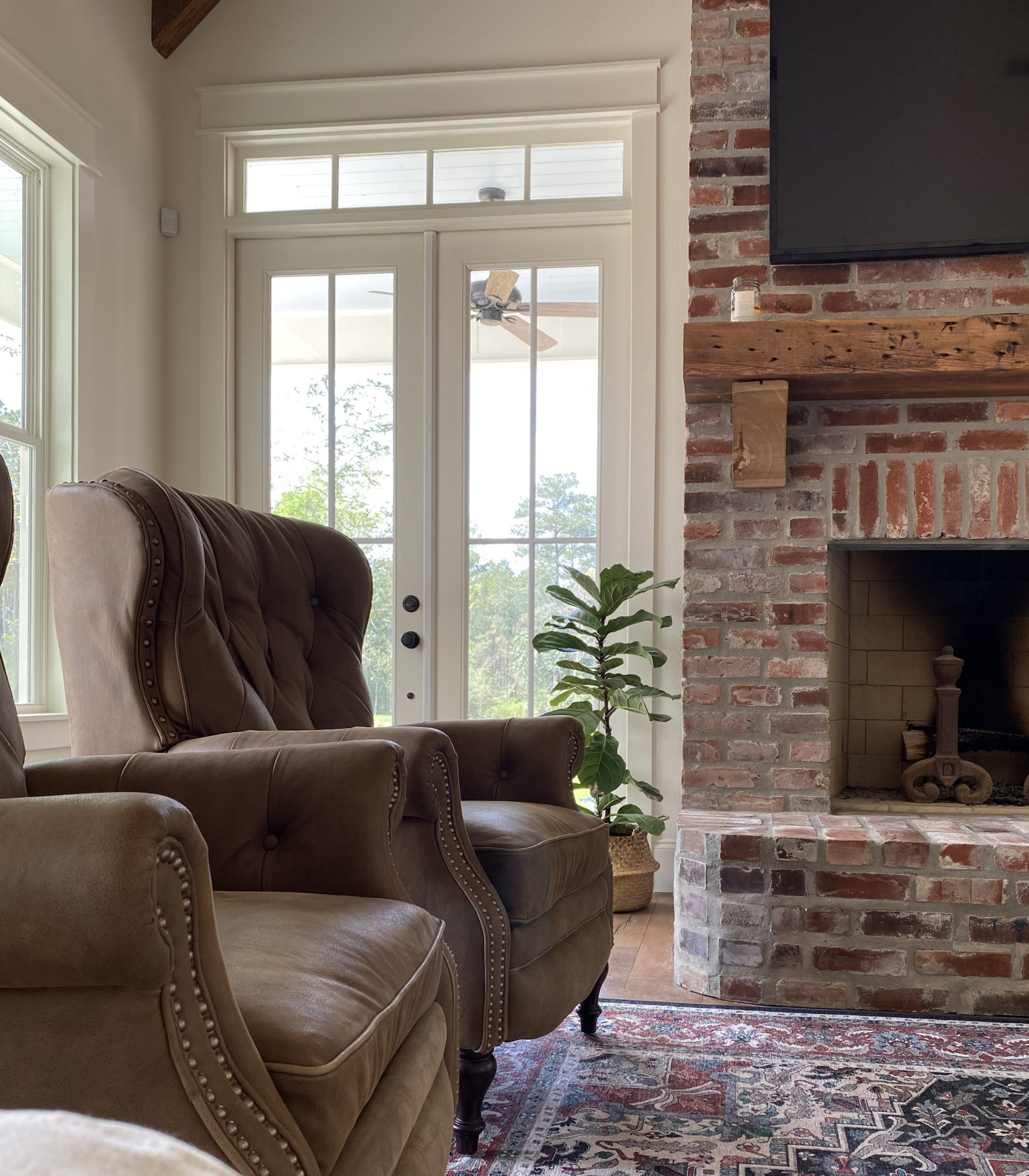 Home on magnolia hill, leather chairs, ruggable, brick fireplace, fiddle leaf fig, transom window, french doors