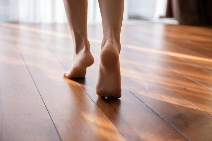 Femme marchant pieds nus sur des orteils sur un parquet stratifié