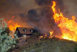 home surrounded by wildfires