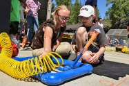 SILVERDALE, Wash. (Aug. 12, 2016) – Corinne Beach, Puget Sound Naval Shipyard and Intermediate Maintenance Facility (PSNS & IMF) K-12 STEM Outreach Coordinator, explains why the pressure gauge must reach 40 psi before the child, enrolled in the Bangor School Age Care Program, can launch his pneumatic rocket during a STEM outreach project coordinated by Naval Sea Systems Command and PSNS & IMF. The Navy is actively seeking candidates well versed and qualified in STEM through programs such as the Navy Reserve Officers Training Corps, the Naval Academy, the Nuclear Propulsion Officer Candidate Program and the Civil Engineer Collegiate Program. (U.S. Navy photo by Mass Communication Specialist 1st Class Cory Asato/Released)