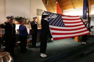 OAK HARBOR, Wash. (Dec. 7, 2016) Petty Officer 2nd Class Carrie McGhee and Petty Officer 2nd Class Michael Berrera hold up the national ensign during a Pearl Harbor commemoration in the base chapel of Naval Air Station Whidbey Island. The event marked the 75th anniversary of the Dec. 7, 1941 Japanese attack on Pearl Harbor. (U.S. Navy photo by Petty Officer 2nd Class John Hetherington/Released)