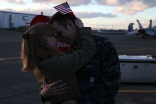 161230-N-DC740-077 OAK HARBOR, Wash. (Dec. 30, 2016) Intelligence Specialist 1st Class, Electronic Attack Squadron 130, hugs his wife after returning home from deployment at Naval Air Station Whidbey Island. Electronic Attack Squadron 130 conducted electronic warfare operations in the 5th Fleet area of responsibility while embarked on USS Dwight D. Eisenhower (CVN 69). (U.S. Navy photo by Mass Communication Specialist 2nd Class John Hetherington/Released)