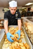 170502-N-EC099-019 SILVERDALE, Wash. (May 2, 2017) Culinary Specialist 2nd Class Roel Caballero, assigned to Naval Base Kitsap's Trident Inn Galley, seasons and mixes sliced potatoes in preparation of lunch. Culinary Specialists operate and manage dining facilities and living quarters for Sailors and Marines in the U.S. Navy. (U.S. Navy photo by Mass Communication Specialist 3rd Class Charles D. Gaddis IV/Released)
