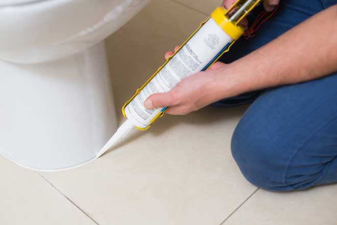 Plumber Caulking Around The Base Of A Toilet