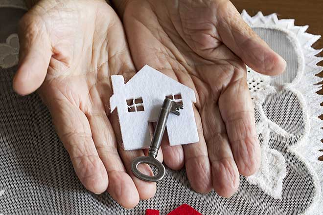 Elderly Person Holding Key to House