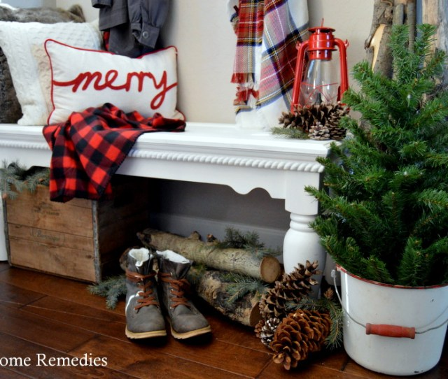 A Cozy Farmhouse Christmas Entryway With Plaids And Patterns For A Warm Rustic Feel