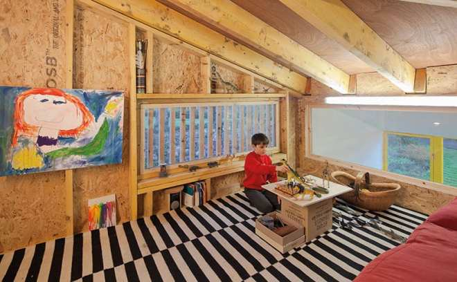 The mezzanine, nicknamed 'the treehouse' by the children, has been left with its rough-and-ready OSB boards exposed, which suits the look and feel of the play area.