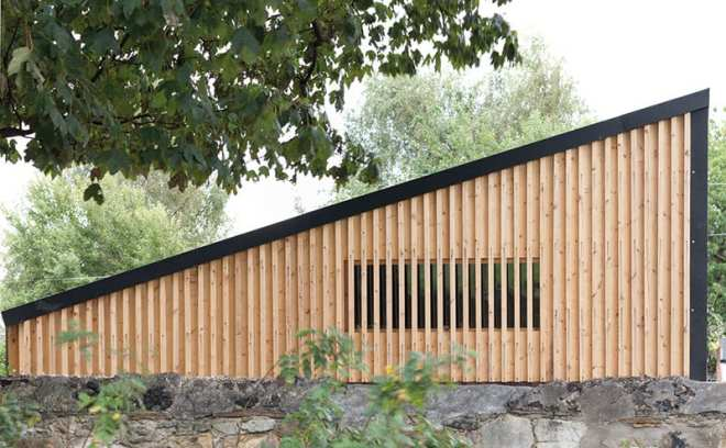 The window is hidden behind the strips of larch cladding. The sharp edges and clean profile of the roof offers an interesting contrast with the rustic buildings and tin shacks that inspired it