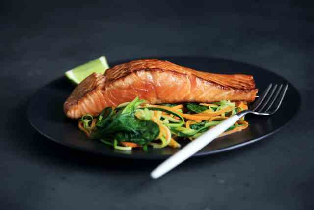 A plate of wild salmon shown which is another of 32 foods that burn belly fat fast