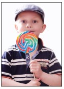 A boy tastes a candy on a stick.