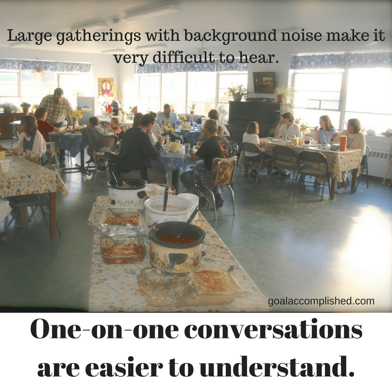 Large group of people eating: one on one conversations are easier for the hearing impaired to understand